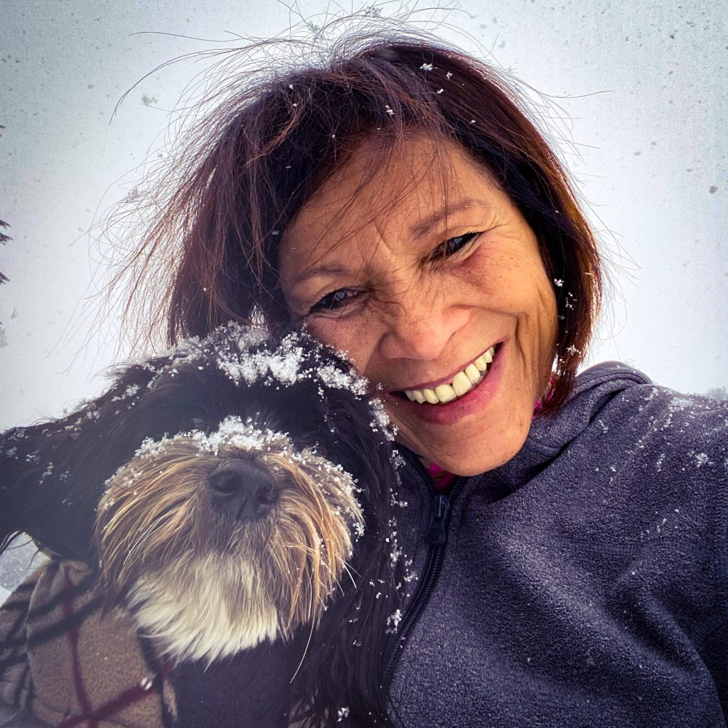 a close up portrait of a woman and her service dog. The dog has snow on his face. The woman is smiling