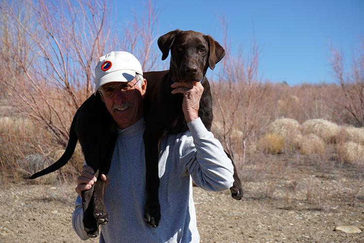 man holding dog on shoulders