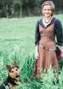 A woman standing in the grass next to her german shepherd