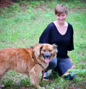 A woman kneeling in the grass next to her brown fluffy dog