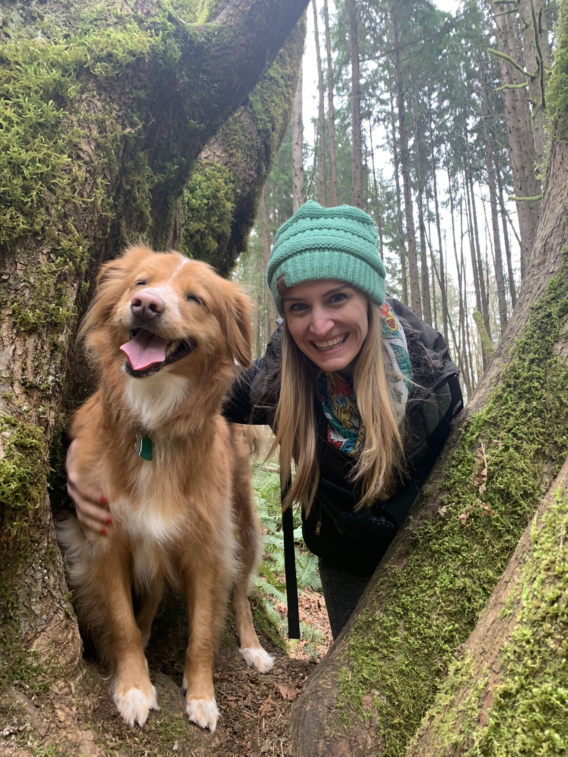 woman in hat in a tree with blonde medium hair dog