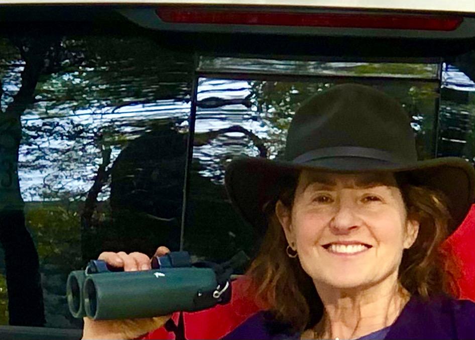 woman in hat holding binoculars