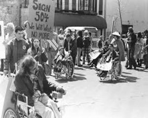 """a black and white image of disabled activists during the disability rights movement protesting in the street. One person holds up a sign reading """"sign 504, we will wait no more"""""""