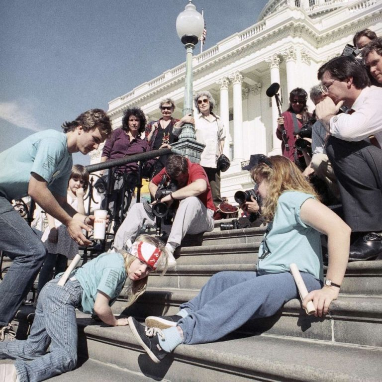 a group of disabled activists climbing up the steps of the US capitol. Some on their hands and feet, others standing during the capitol crawl