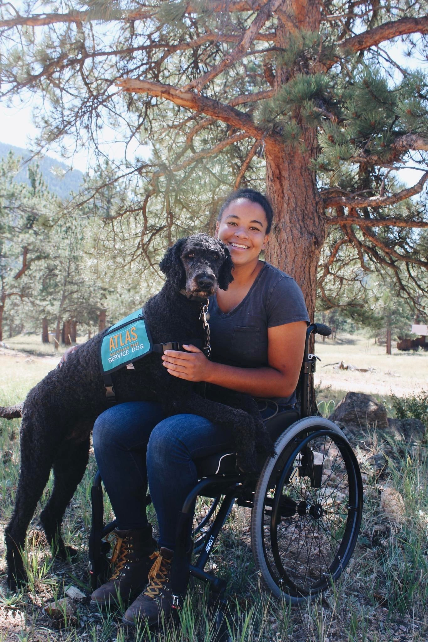 A young woman in a wheelchair with her black poodle service dog with both his paws on her lap